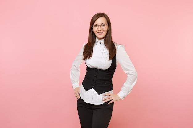 Młody radosny udanego biznesu kobieta w czarnym garniturze, białej koszuli i okularach stojący na białym tle na pastelowym różowym tle. szefowa. koncepcja bogactwa kariery osiągnięcia. skopiuj miejsce na reklamę.