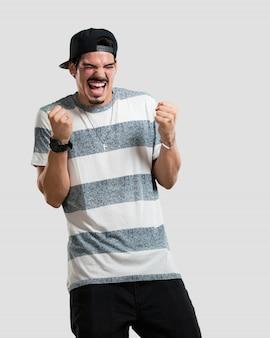 Młody raper człowiek bardzo szczęśliwy i podekscytowany, podnoszenie broni, świętuje zwycięstwo lub sukces, wygrywając loterii