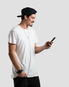 Młody raper człowiek szczęśliwy i zrelaksowany, dotykając telefonu komórkowego, korzystając z internetu i sieci społecznej