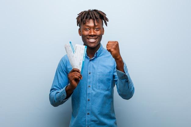 Młody rasta czarny człowiek posiadający bilety lotnicze pokazujące pięść, agresywny wyraz twarzy.