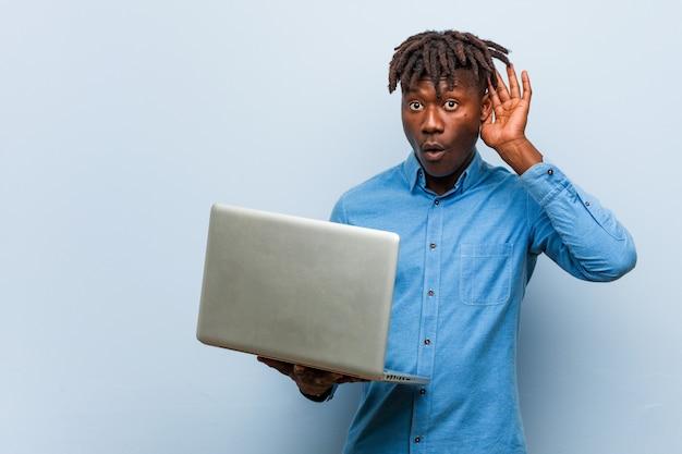 Młody rasta czarny człowiek trzyma laptopa próbuje słuchać plotek.