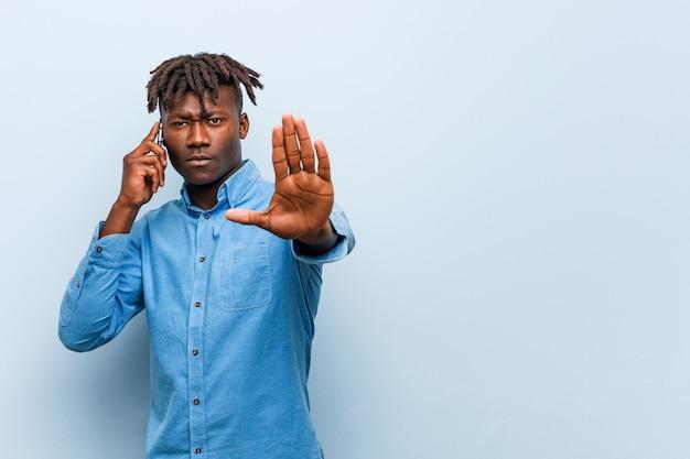 Młody rasta czarny człowiek trzyma telefon stojący z wyciągniętą ręką pokazując znak stop, zapobiegając ci.
