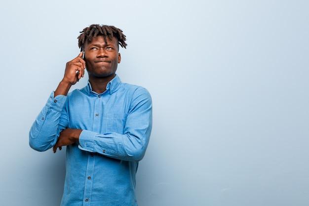 Młody rasta czarny człowiek trzyma telefon uśmiecha się pewnie ze skrzyżowanymi rękami.