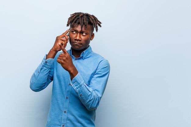 Młody rasta czarny człowiek trzyma telefon uśmiecha się wesoło wskazując palcem wskazującym daleko.