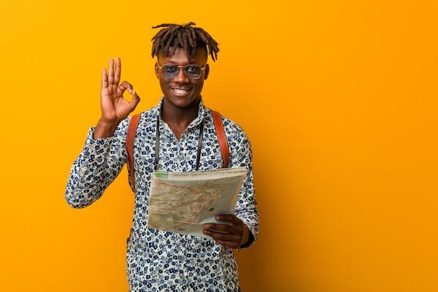 Młody rasta murzyn trzyma mapę wesoły i pewny siebie, pokazując ok gest.