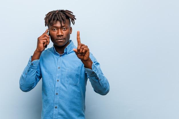 Młody rasta murzyn trzyma telefon pokazuje liczbę jeden z palcem.