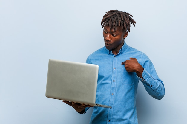 Młody rasta murzyn z laptopem zaskoczony, wskazując na siebie, uśmiecha się szeroko.