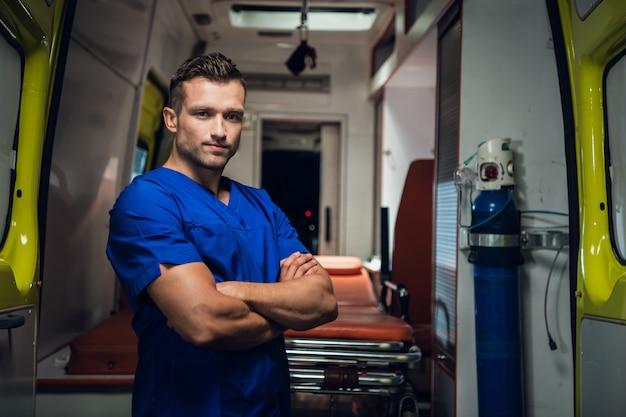Młody ratownik medyczny patrząc w kamerę i uśmiechnięty, pogotowie ratunkowe w tle.