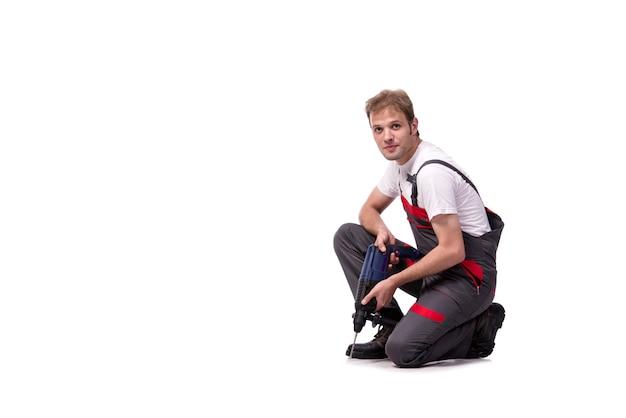 Młody repairman z świder perforator odizolowywającym na bielu