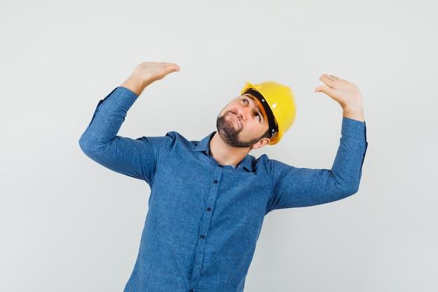 Młody robotnik w koszuli, z hełmem podnoszącym ręce i pochylając głowę, by się bronić