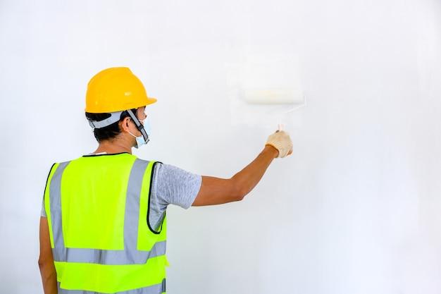 Młody robotnik z azji jako malarz do malowania ścian w domu i za pomocą wałka do malowania białego podkładu na placu budowy