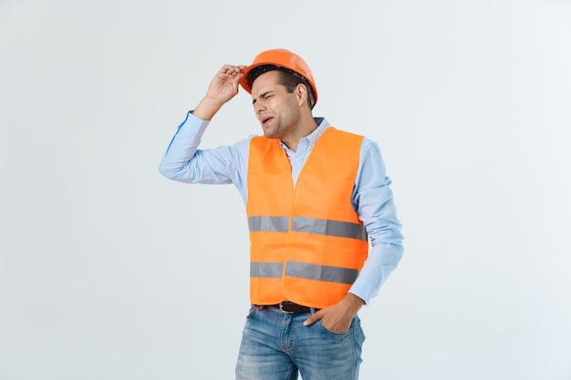 Młody robotnik zirytowany wściekłym gestem. negatywne wyrażenie na białym szarym tle.