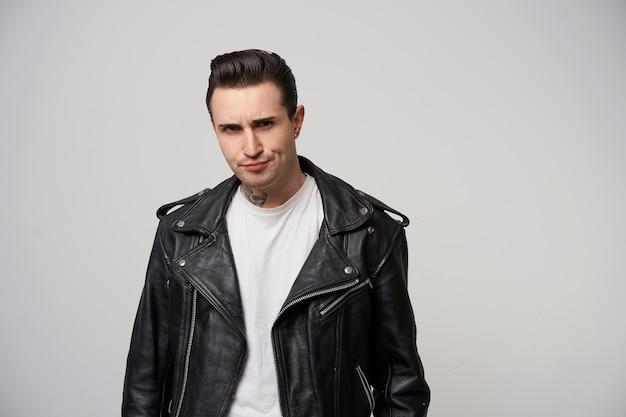 Młody rocker, buntownik, motocyklista ze stylową fryzurą w briolinie