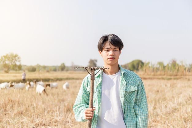 Młody rolnik azjatycki mężczyzna stojący z widłami patrząc na kamery rozmazane kozy jedzą trawę w polu