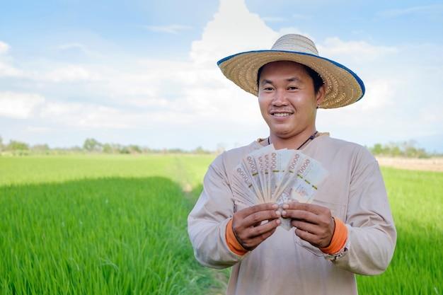 Młody rolnik azjatyckich mężczyzna trzyma pieniądze banknotów na farmie zielonego ryżu.