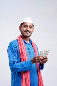 Młody rolnik indyjski pozowanie z walutą na białym tle.