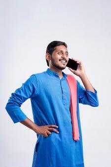 Młody rolnik indyjski rozmawia przez telefon komórkowy na białym tle.