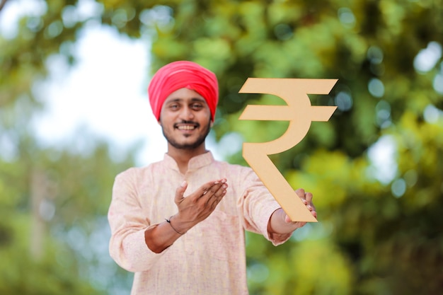 Młody rolnik indyjski, trzymając w ręku symbol rupii.