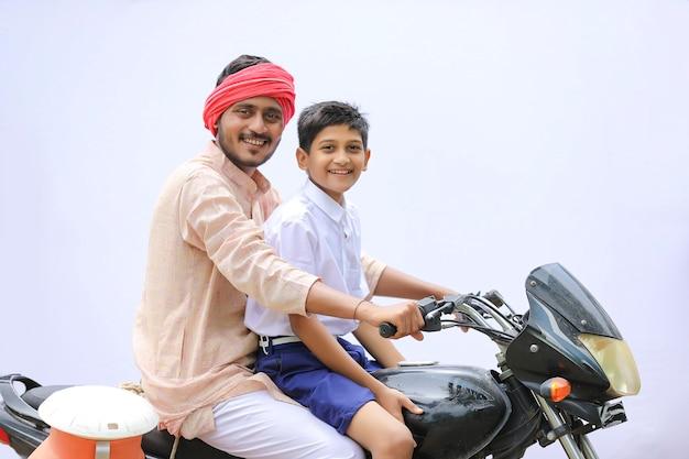 Młody rolnik indyjski upuszcza dziecko do szkoły na rowerze.