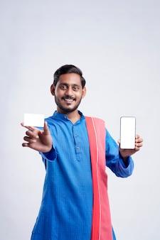 Młody rolnik indyjski wyświetlono karty i smartphone na białym tle.
