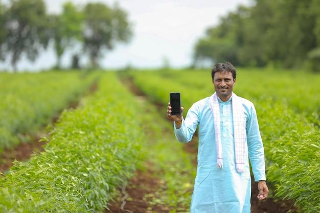 Młody rolnik indyjski wyświetlono smartphone w dziedzinie rolnictwa.