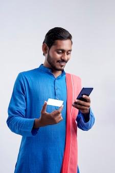 Młody rolnik indyjski za pomocą smartfona i karty bankowej na białym tle.