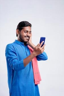 Młody rolnik indyjski za pomocą smartfona na białym tle.