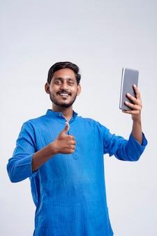 Młody rolnik indyjski za pomocą tabletu i dając wyraz na białym tle.