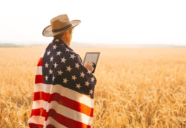 Młody rolnik kaukaski energicznie uniósł amerykańską flagę na polu