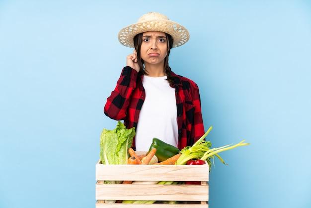 Młody rolnik kobieta trzyma świeże warzywa w drewnianym koszu, mając wątpliwości