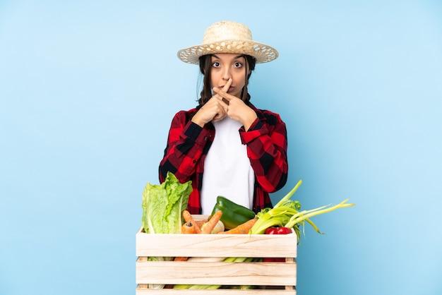 Młody rolnik kobieta trzyma świeże warzywa w drewnianym koszu wykazujące znak gestu ciszy