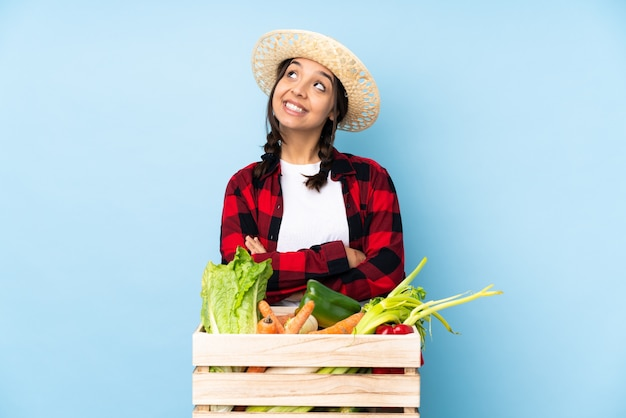 Młody rolnik kobieta trzymająca świeże warzywa w drewnianym koszu patrząca w górę i uśmiechnięta