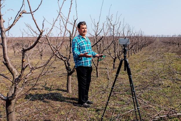 Młody rolnik przycinanie drzew owocowych na wiosnę. blogger influencer nagrywający koncepcję wideoblogu mówiącego o smartfonie