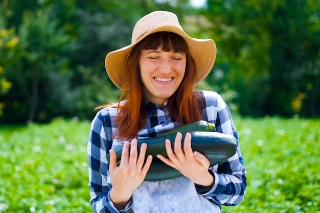 Młody rolnik trzymający cukinię i drewniane pudełko wypełnione świeżymi warzywami