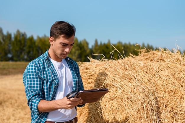 Młody rolnik z tabletem obok stogu siana w polu, żniwa, przemysł, rolnictwo, wycena, biznes