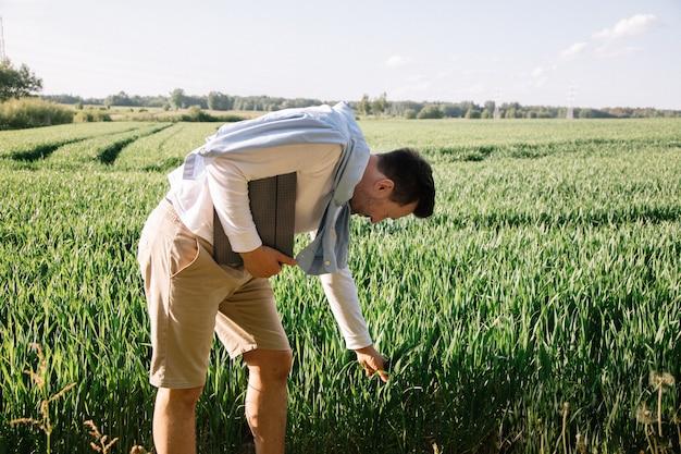 Młody rolnik z teczką pod pachą 40-latek sprawdzający swój plon pastewny,