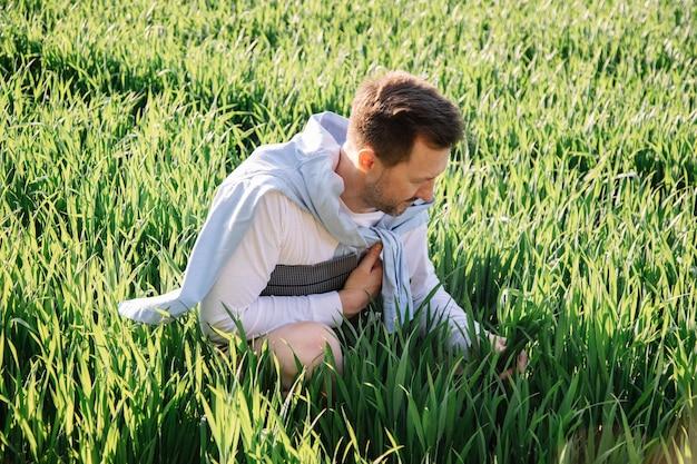 Młody rolnik z teczką pod pachą, siedzący na polu, 40-latek, sprawdzający swój plon pastewny