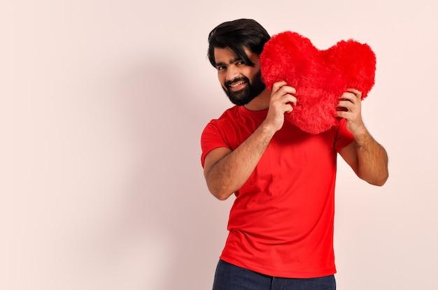 Młody romantyczny mężczyzna pokazujący poduszkę duże czerwone serce