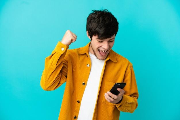 Młody rosjanin na białym tle na niebieskim tle, używający telefonu komórkowego i wykonujący gest zwycięstwa