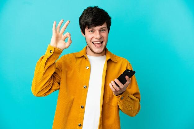 Młody rosjanin na białym tle na niebieskim tle za pomocą telefonu komórkowego i robi znak ok