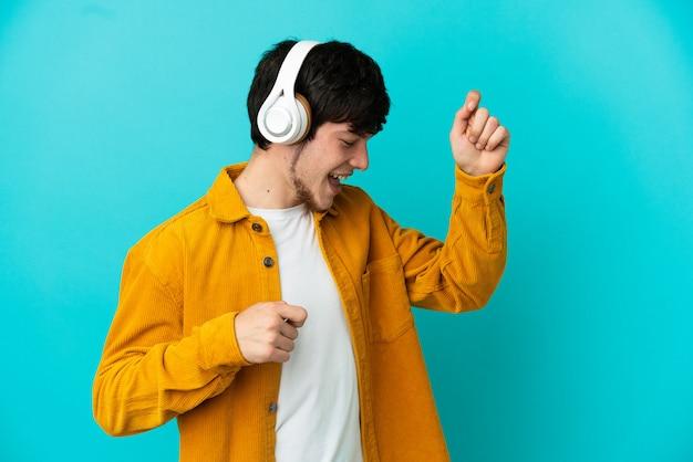 Młody rosjanin odizolowany na niebieskim tle słuchając muzyki i tańcząc
