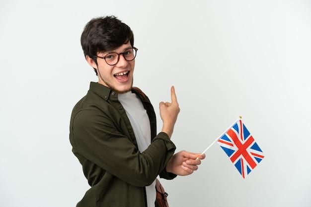 Młody rosjanin trzymający flagę wielkiej brytanii na białym tle wskazującą do tyłu