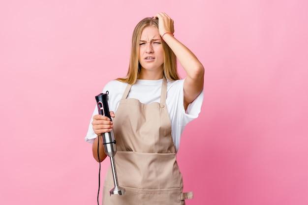Młody rosyjski kucharz kobieta trzyma mikser elektryczny na białym tle zmęczony i bardzo senny trzymając rękę na głowie