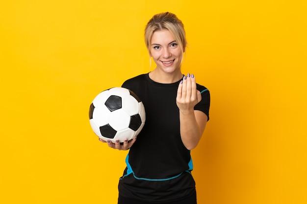 Młody rosyjski piłkarz kobieta na białym tle na żółtym tle zapraszając do przyjścia z ręką. cieszę się, że przyszedłeś