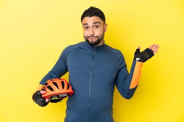 Młody rowerzysta arabski mężczyzna na białym tle na żółtym tle mający wątpliwości podczas podnoszenia rąk