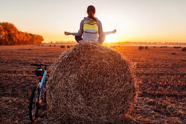 Młody rowerzysta medytuje siedząc na stogu siana po przejażdżce. kobieta o odpoczynku praktykowania jogi w jesiennym polu. koncepcja rekreacji sportowej
