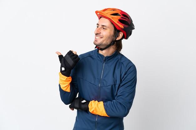 Młody rowerzysta mężczyzna na białym tle, wskazując na bok do przedstawienia produktu