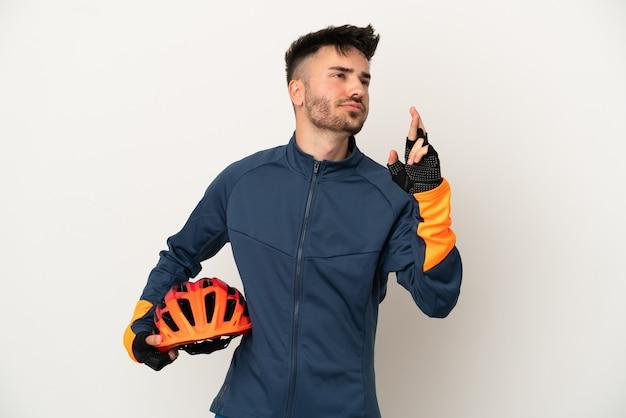 Młody rowerzysta mężczyzna na białym tle z palcami skrzyżowanymi i życzącymi wszystkiego najlepszego