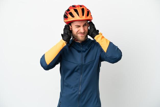 Młody rowerzysta na białym tle sfrustrowany i zakrywający uszy