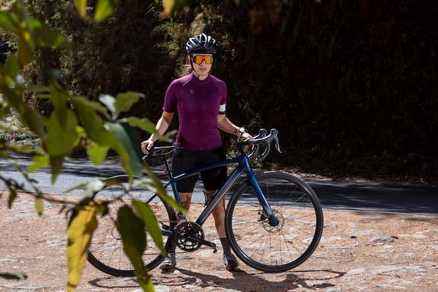 Młody rowerzysta odpoczywa z rowerem na poboczu drogi, ubrany w kask i okulary przeciwsłoneczne